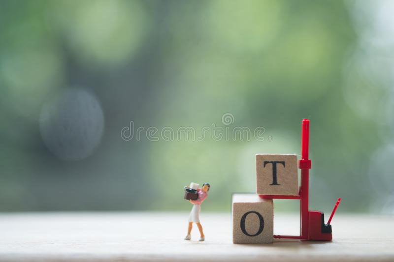 Miniature people: Woman working hard work and with text block. `OT` mean overtime with nature background. Overtime concept royalty free stock photo
