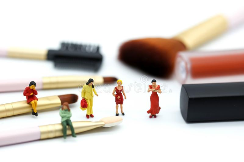 Miniature people: womans and friend sitting on cosmetic bottle u stock photo