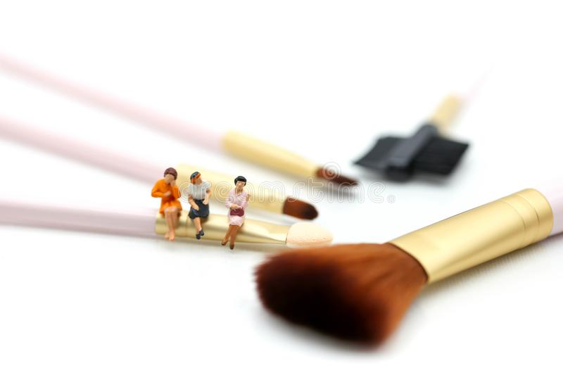 Miniature people: womans and friend sitting on cosmetic bottle u royalty free stock images
