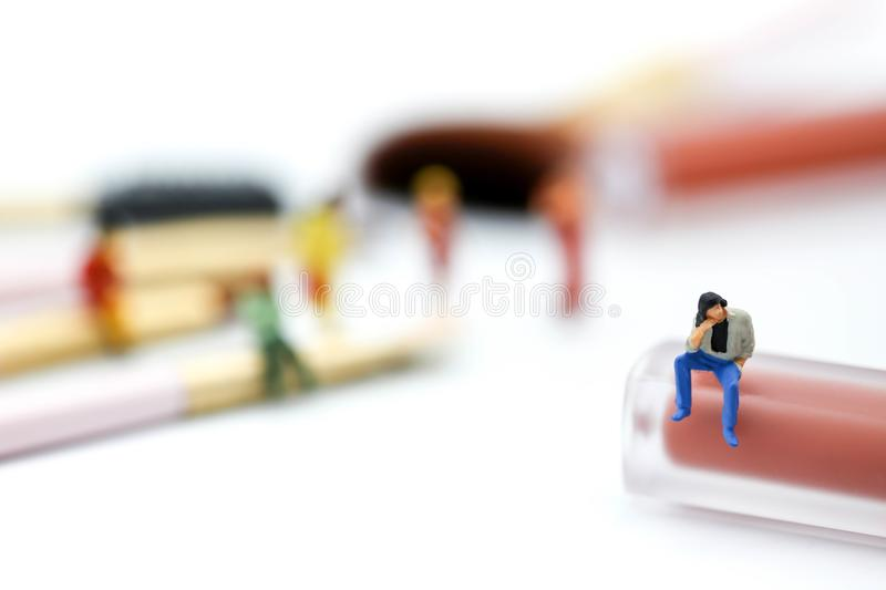 Miniature people: womans and friend sitting on cosmetic bottle u stock image