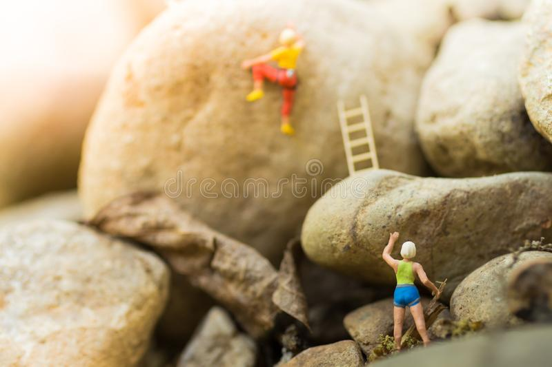 Miniature people : Women are playing high climbing sport. Used as a background for holiday adventure travel business concept.  royalty free stock image