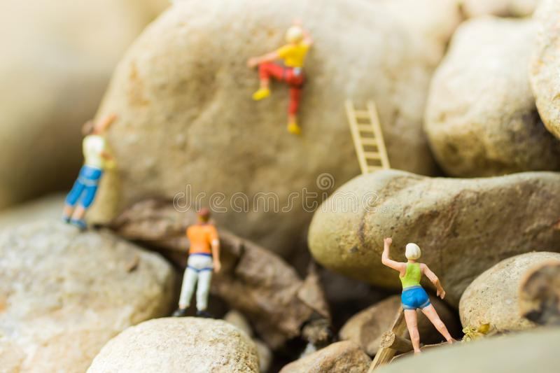 Miniature people : Women are playing high climbing sport. Used as a background for holiday adventure travel business concept.  royalty free stock photography