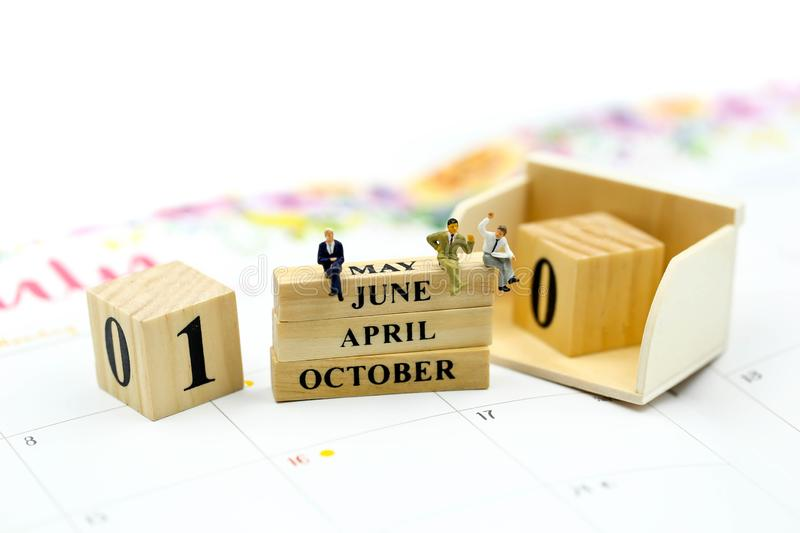 Miniature people : Wooden block calendar date and mounth with miniworld.  stock photo