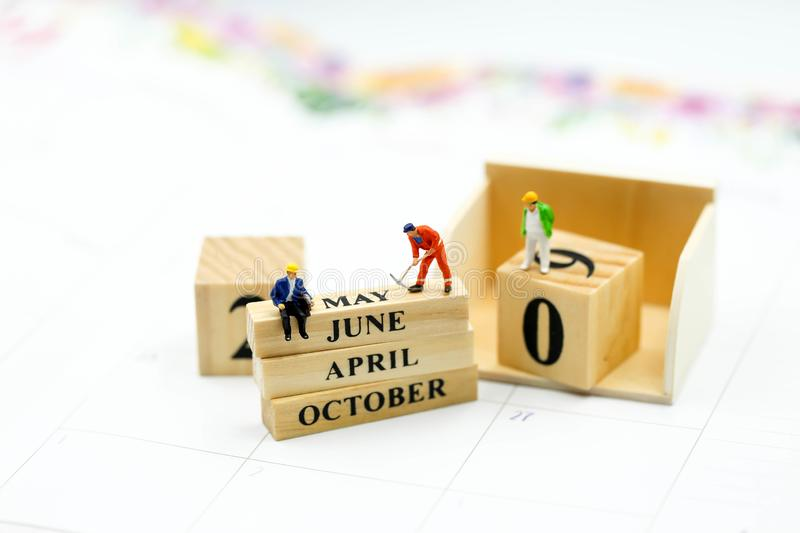 Miniature people : Wooden block calendar date and mounth with miniworld.  royalty free stock photo