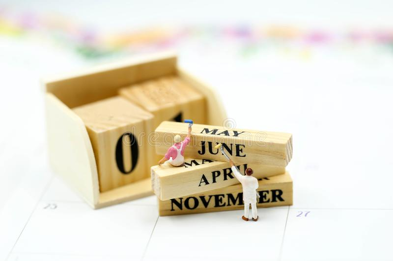 Miniature people : Wooden block calendar date and mounth with miniworld.  stock photos