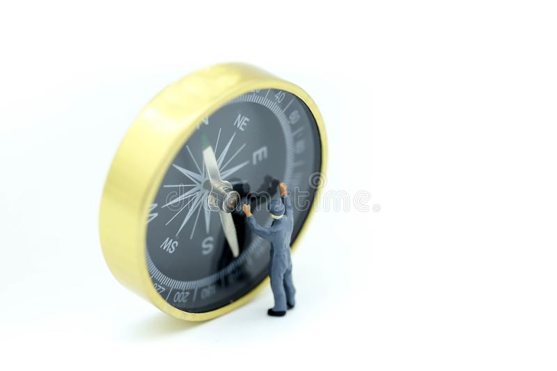 Miniature people : worker cleaning compass. royalty free stock photos