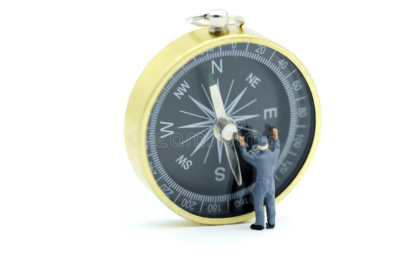 Miniature people : worker cleaning compass. royalty free stock images