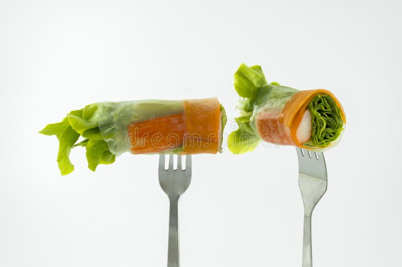Miniature people worker digging into the salad of fresh vegetablSalad of fresh vegetables rolls on a fork isolated on white backgr. Salad of fresh vegetables royalty free stock photos