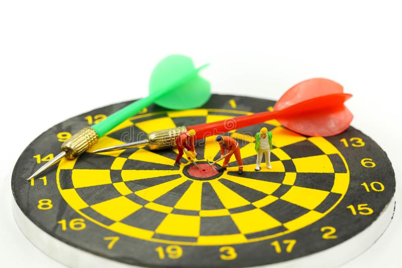Miniature people : worker digging on the target on dart board, c stock images