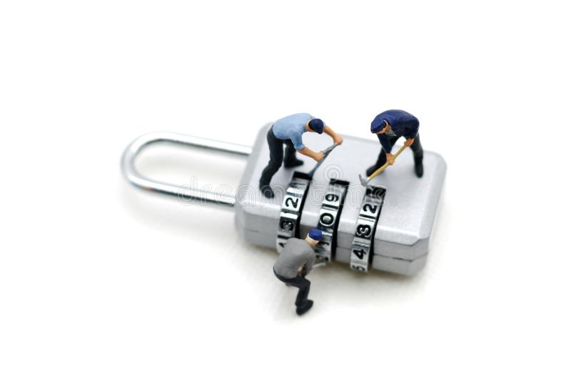 Miniature people: Worker hacking in padlock security. concept. For data security breach, risk and hacker attack stock photography