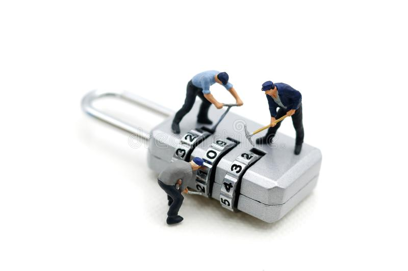 Miniature people: Worker hacking in padlock security. concept. For data security breach, risk and hacker attack stock photo