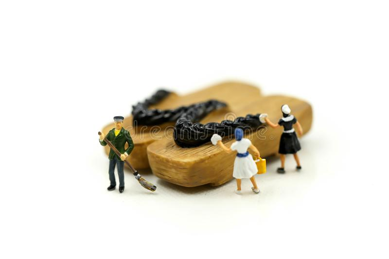 Miniature people : worker,maid cleaning Japanese wooden shoes g. Eta royalty free stock image