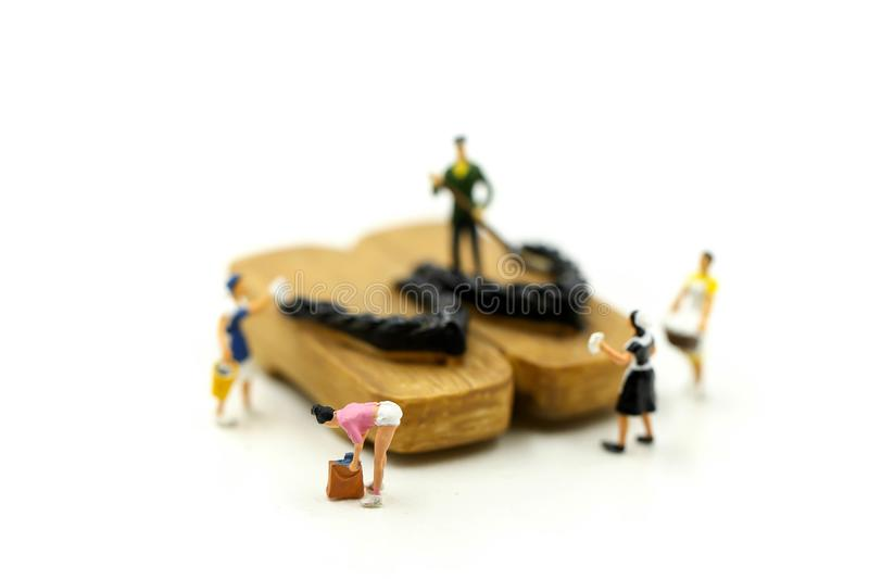 Miniature people : worker,maid cleaning Japanese wooden shoes g. Eta royalty free stock images