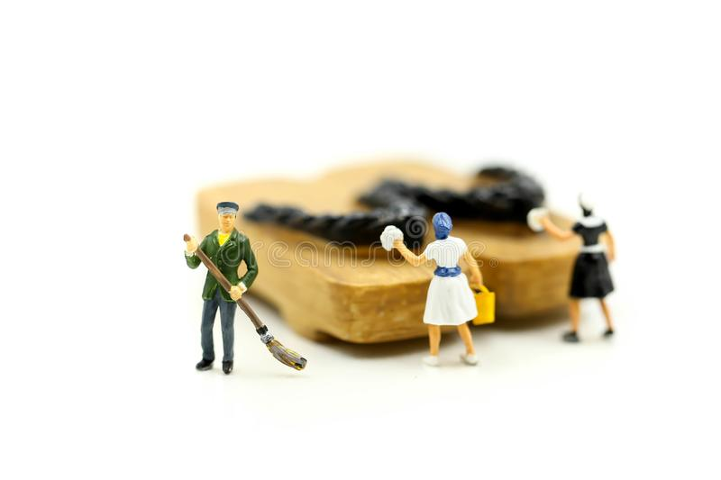Miniature people : worker,maid cleaning Japanese wooden shoes g. Eta royalty free stock photo