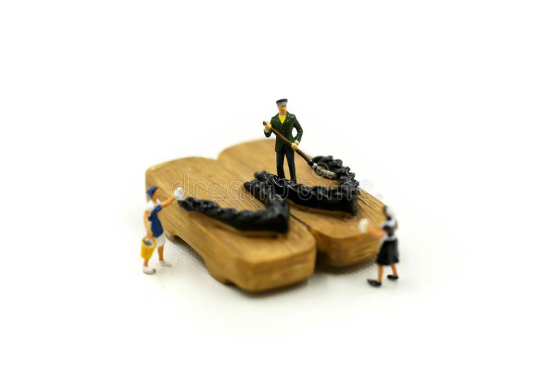 Miniature people : worker,maid cleaning Japanese wooden shoes g. Eta royalty free stock photography