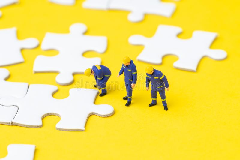Miniature people worker team or staff help finishing white jigsaw puzzle pieces on yellow background with copy space, teamwork,. Problem solution or business royalty free stock images