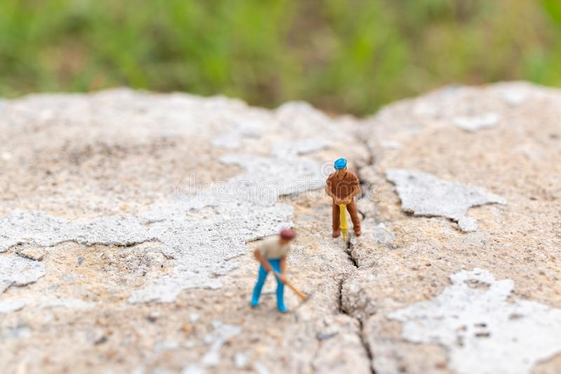 Miniature people : Worker team working on  concrete with cracked. Team work  concept royalty free stock image