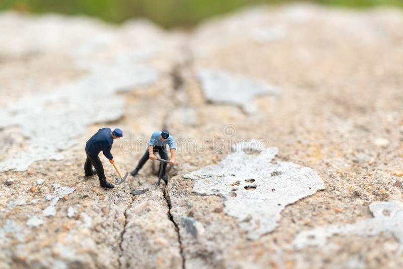 Miniature people : Worker team working on  concrete with cracked. Team work  concept stock photography