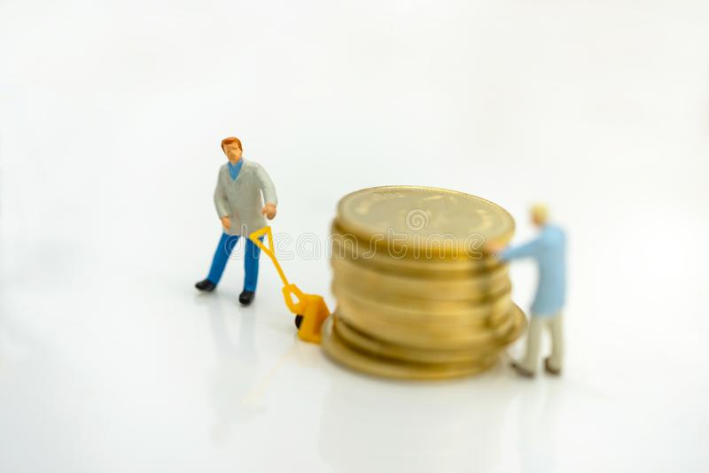 Miniature people: Worker transportation golden coin royalty free stock image