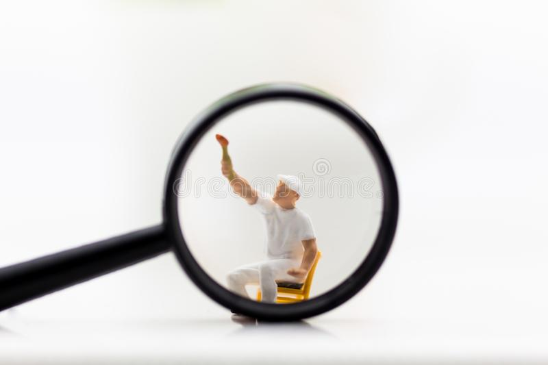 Miniature people: Worker are wiping the glass of a magnifying glass. Image use for background business concept.  stock photo