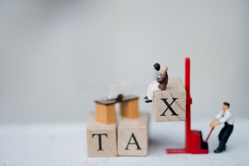 Miniature people worker wood word with TAX by forklift stock photography