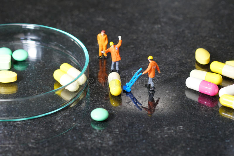 Miniature people - The worker at work with medicine pills. Miniature people - The worker at work with the medicine pills royalty free stock photos