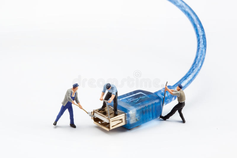Miniature people - workers fixing a USB plug. On white background royalty free stock images