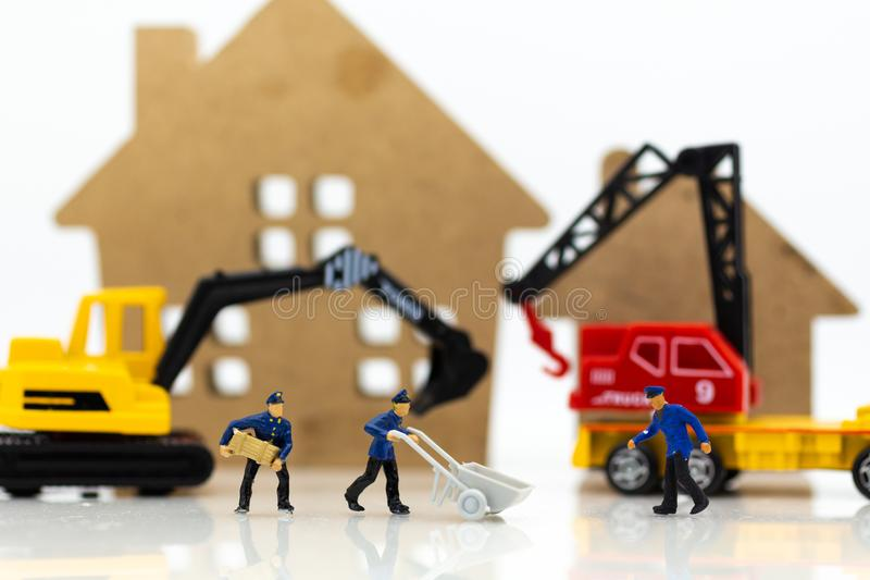 Miniature people: Workers help to moving crates for building home . Image use for construction, business concept.  royalty free stock image