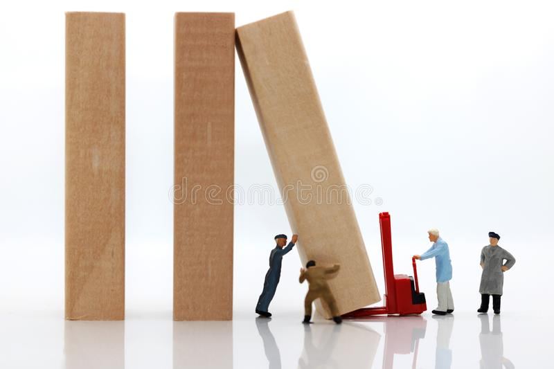 Miniature people: Workers team stopping the domino effect, stock photo