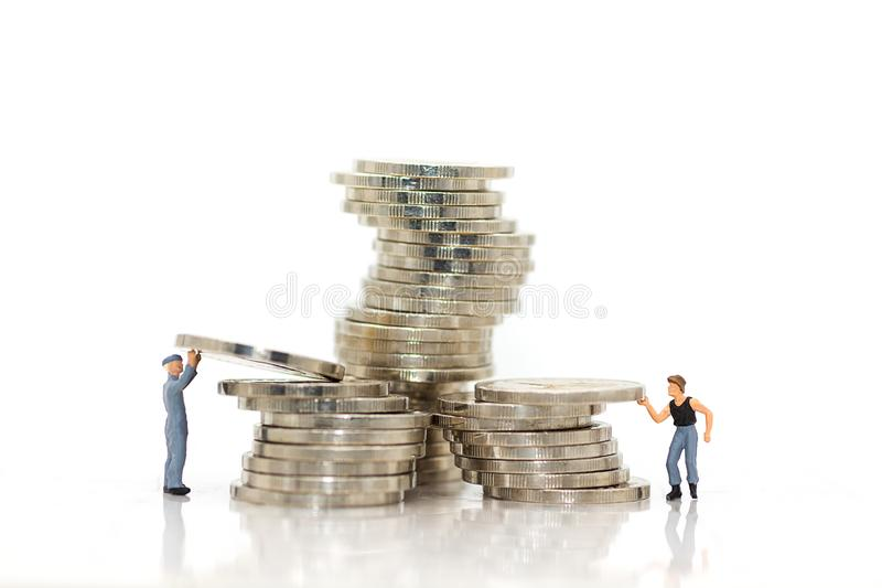 Miniature people : Workers work hard to keep money for everyday use. Miniature people : Workers work hard to keep money for everyday use and family royalty free stock image