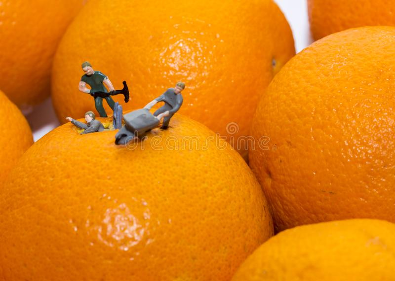 Miniature people working on the extraction of orange juice. Concept royalty free stock image