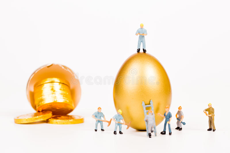 Miniature people working with gold egg. On white background royalty free stock photography