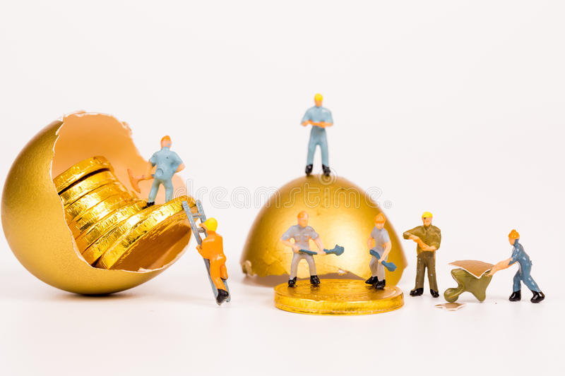 Miniature people working in gold mine. On white background royalty free stock photo