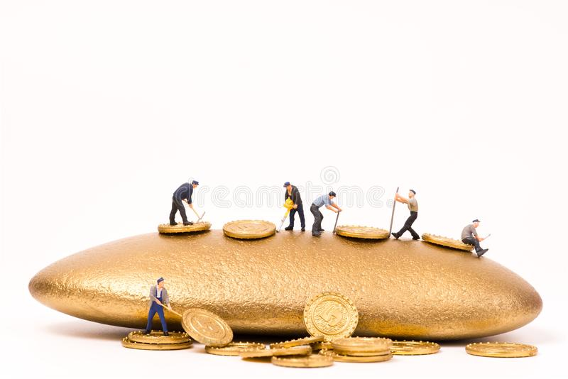 Miniature people working in gold mine. On white background stock image