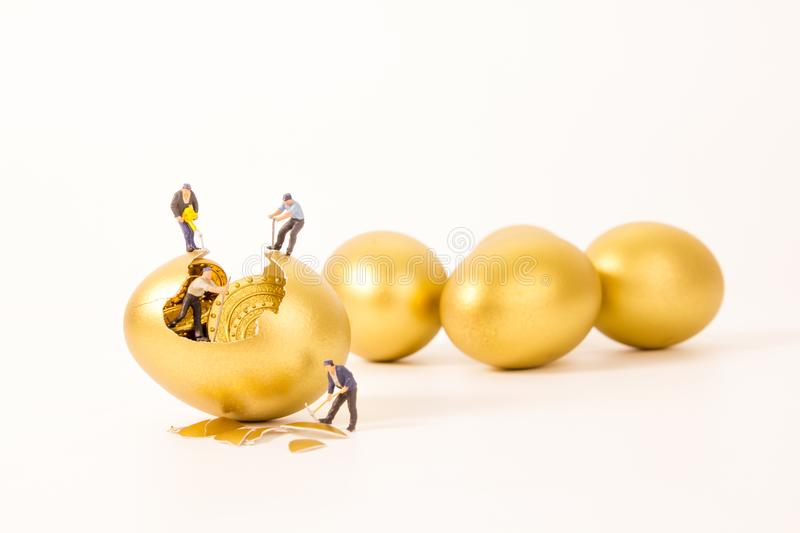Miniature people working with golden egg. Business concept royalty free stock photos