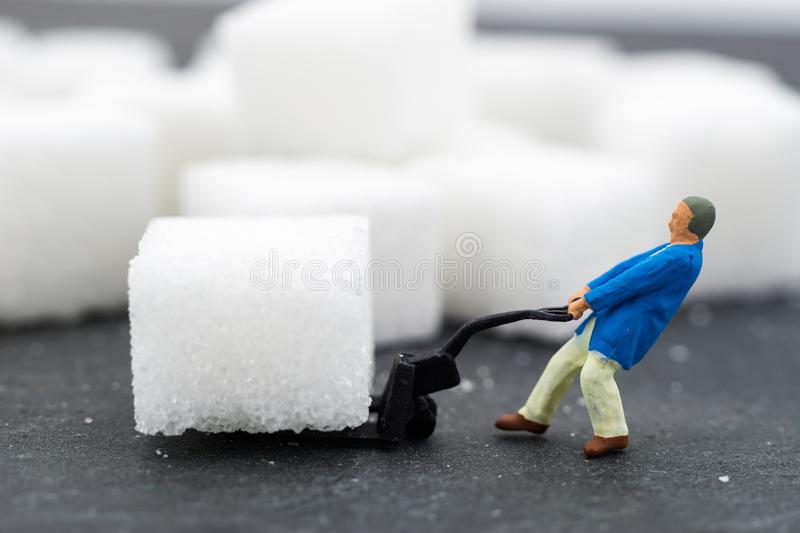 Miniature people Working with sugar. Health care concept. Diet, fat and diabetes. Health care concept royalty free stock image