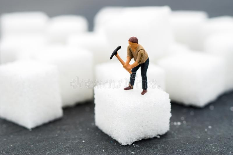 Miniature people Working with sugar. Health care concept. Diet, fat and diabetes. Health care concept stock photo