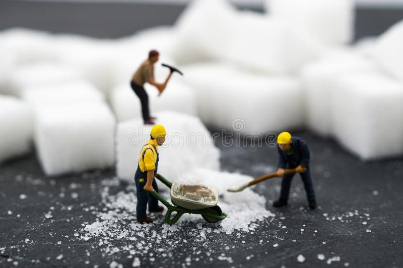 Miniature people Working with sugar. Health care concept. Diet, fat and diabetes. Health care concept stock images