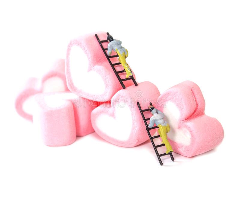 Miniature people working with sweet marshmallow candies ,selective focus royalty free stock photos