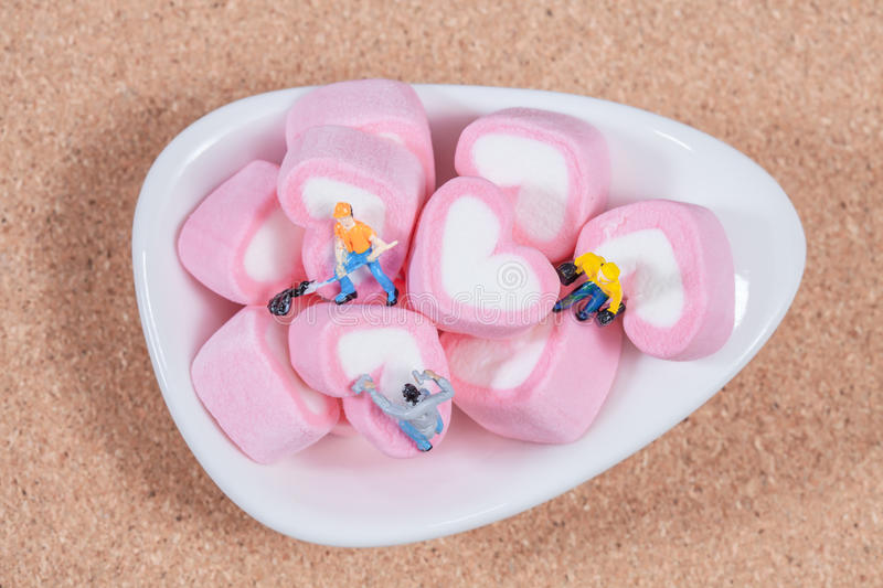 Miniature people working with sweet marshmallow. Candies ,selective focus stock photography