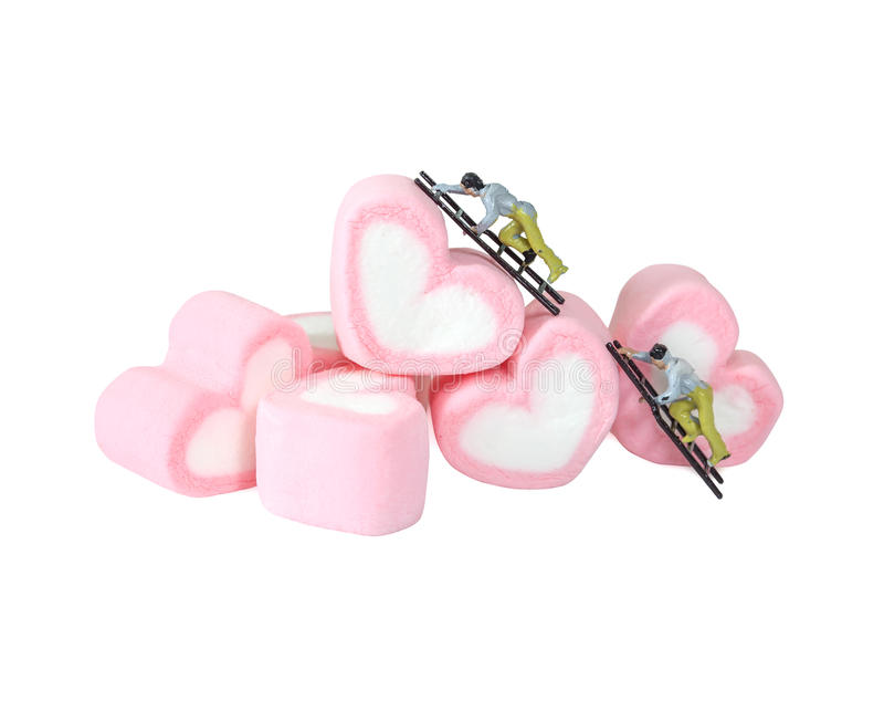 Miniature people working with sweet marshmallow candies ,. Selective focus stock image