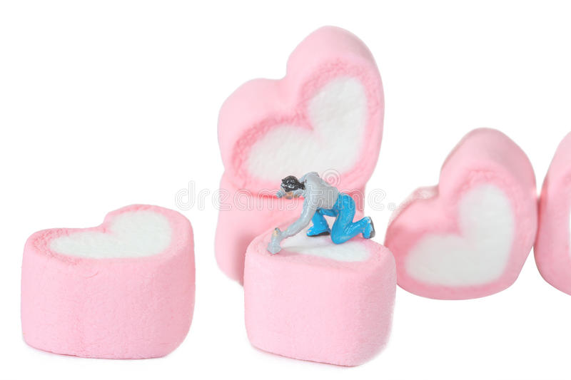 Miniature people working with sweet marshmallow candies ,. Selective focus royalty free stock image