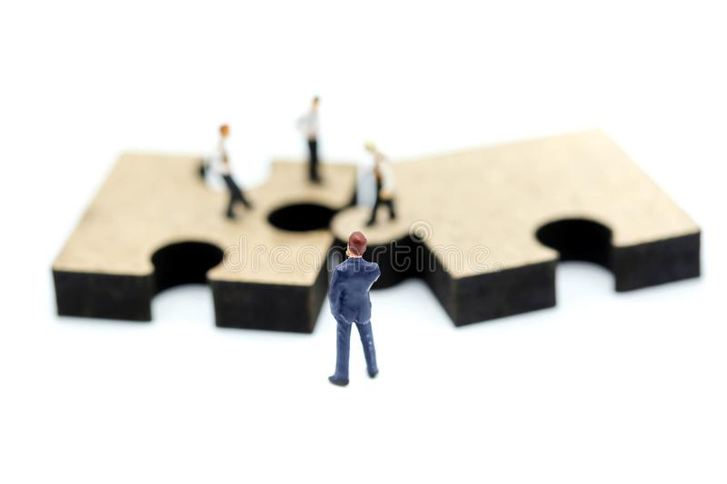 Miniature people : young businessman standing on jigsaw puzzle p stock images