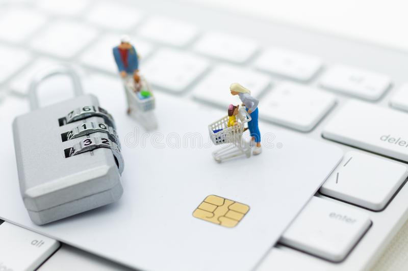 Miniature person: a shopper pushes a shopping cart with credit card. Image use for security of using internet to shopping online. Concept retail business stock photo