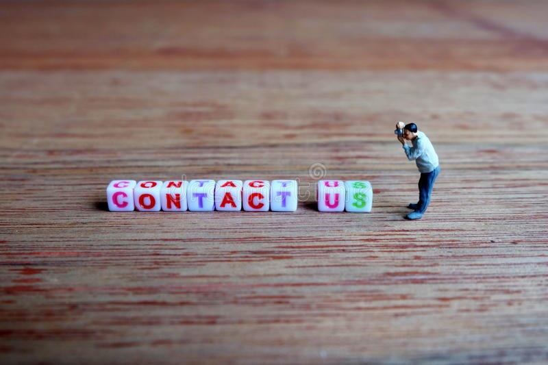 Miniature Photographer, Taking Picture of Contact Us Cubes. royalty free stock images