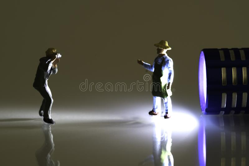 Miniature Photographer taking pictures of a back lit man with apron. Light is a miniature blue flashlight stock images