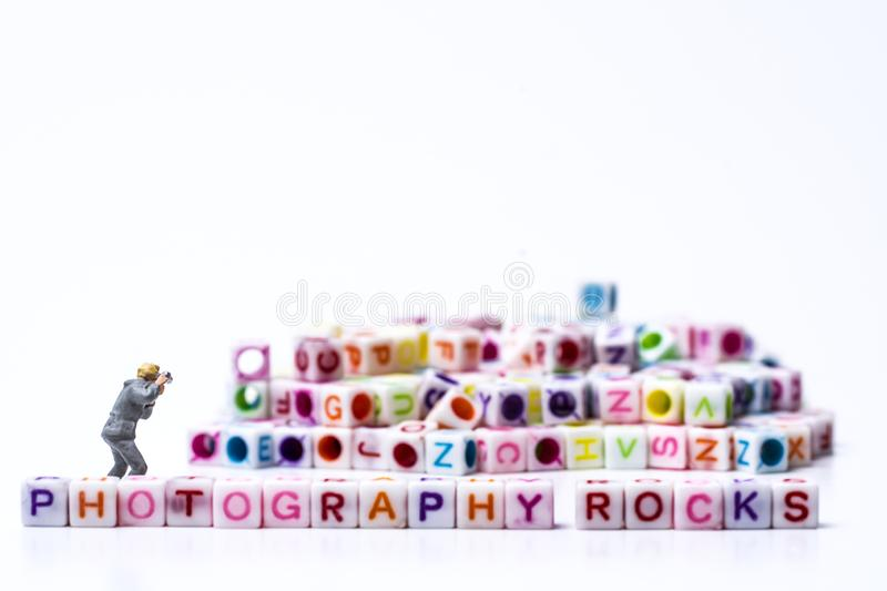 Miniature Photographer taking pictures before a Group Of Letters forming Words Spelling stock images