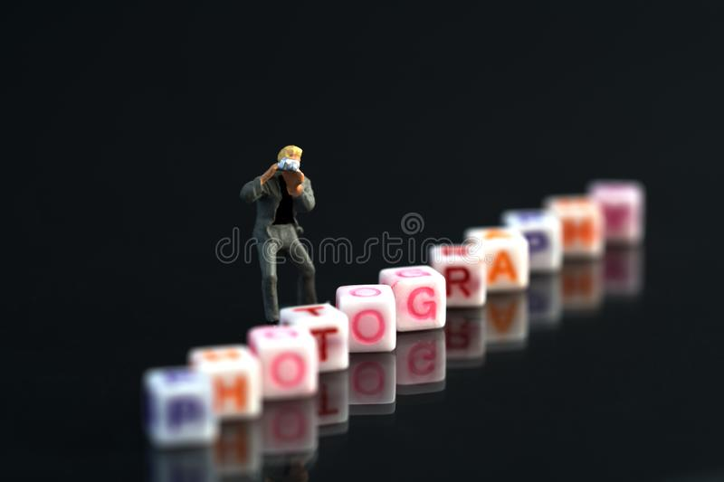 Miniature Photographers taking pictures behind a Group Of Letters forming Word Spelling stock image