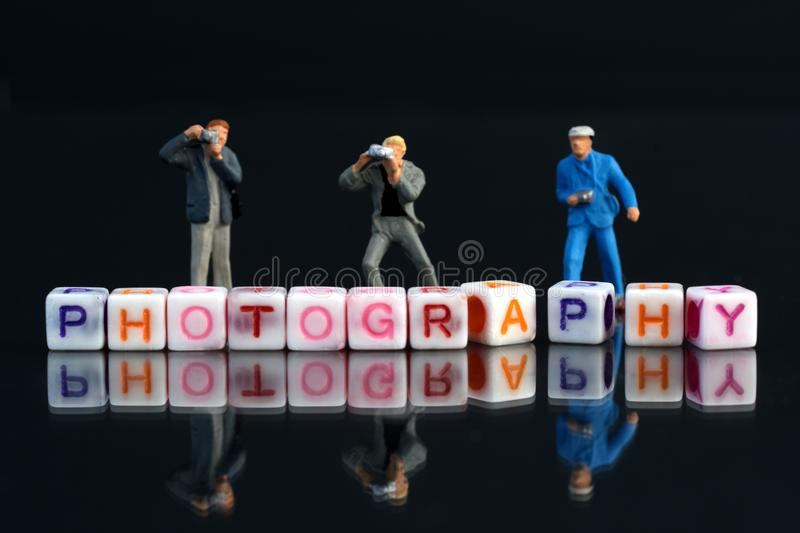 Miniature Photographers taking pictures behind a Group Of Letters forming Word Spelling royalty free stock photos