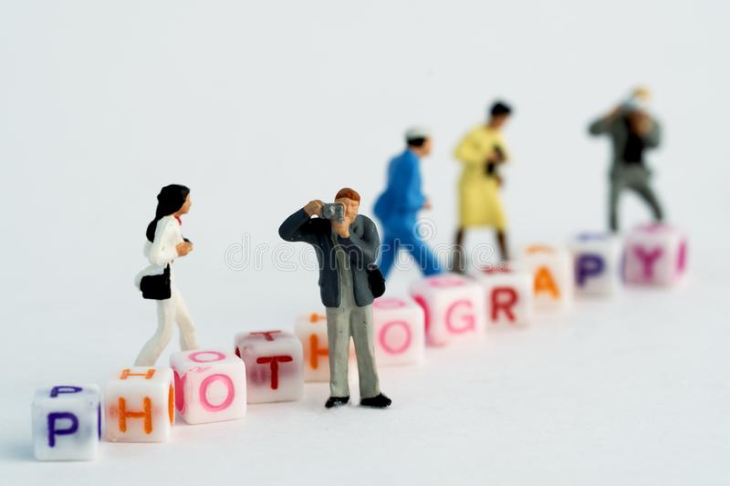 Miniature Photographers taking pictures behind a Group Of Letters forming Word Spelling royalty free stock image